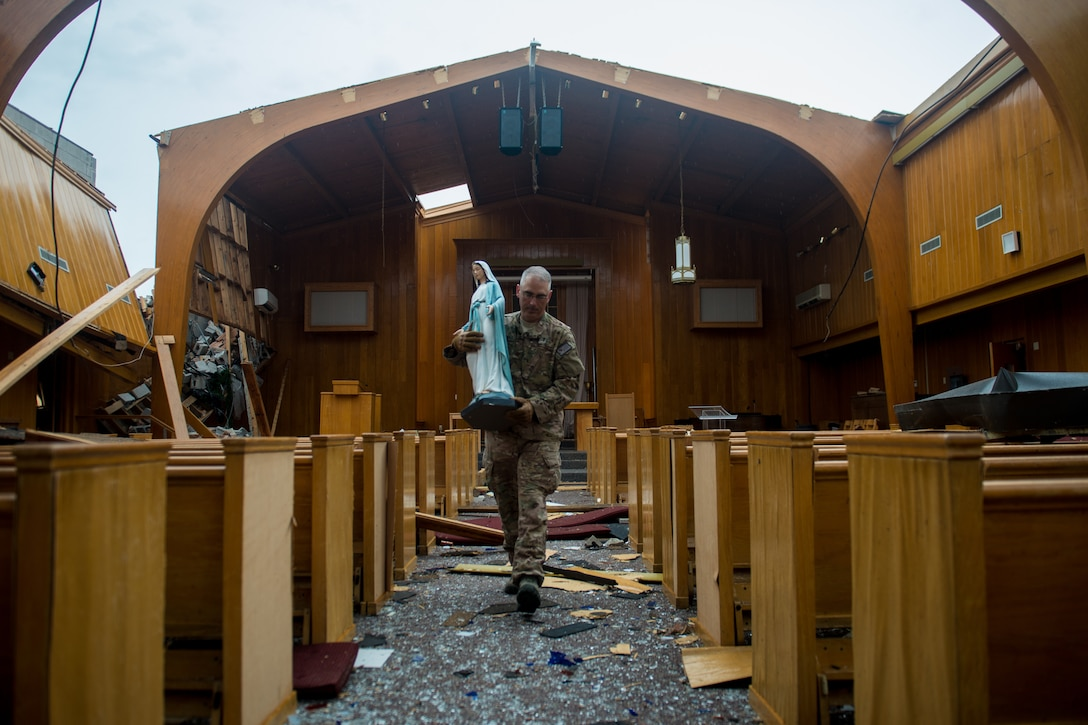 Major Zachary Nash helps carry religious items from a church