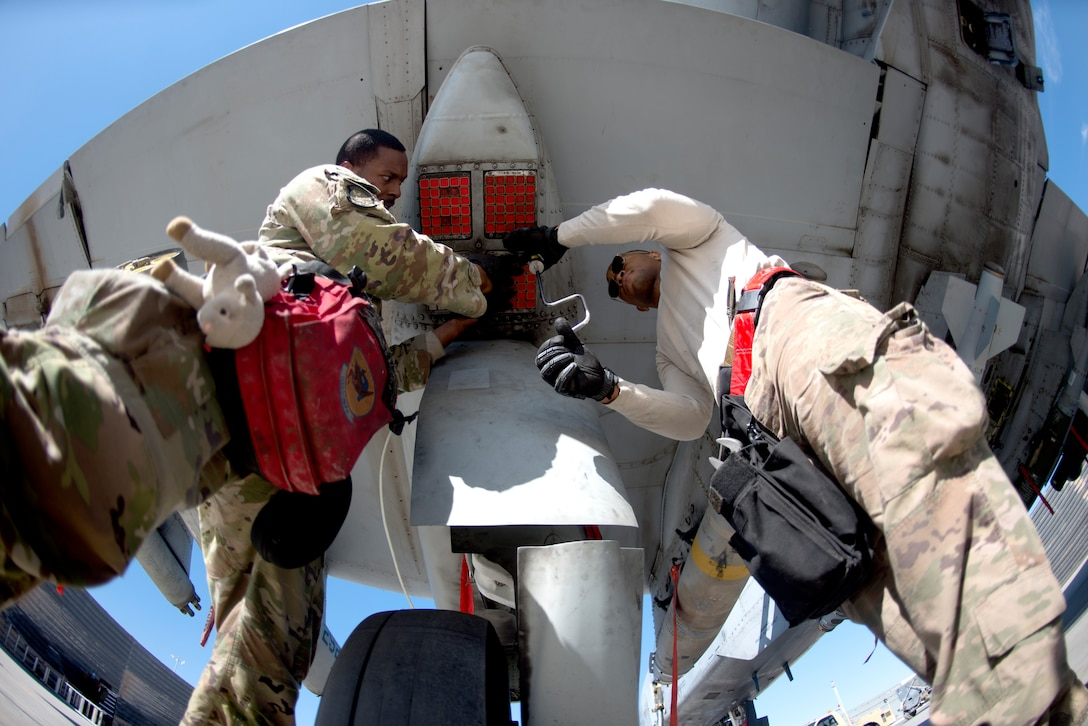 Airmen load munitions onto an A-10 Warthog