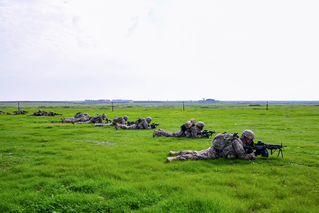 A group of soldiers lie down on the ground in  a row pointing their weapons.