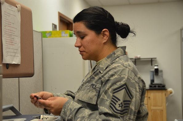 Senior Master Sgt. Livia Almandos, 161st Air Refueling Wing's Equal Employment Opportunity Specialist, displays engraving procedures on a Military Dog-Tag Embossing Machine at Goldwater Air National Guard Base, Phoenix, 06 January, 2019. Almandos volunteered to be the Unit Deployment Manager for the Wing Staff and takes pride of the undertaking as an additional duty in the New Year. (U.S. Air National Guard photo by 1st Lt. Tinashe Machona)