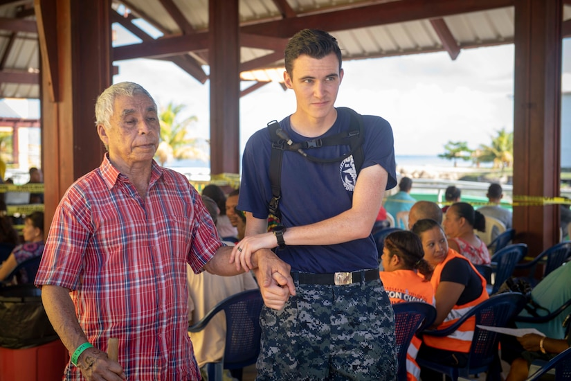 A U.S. service member holds an elderly man's arm while helping him walk to get treatment at a medical clinic.