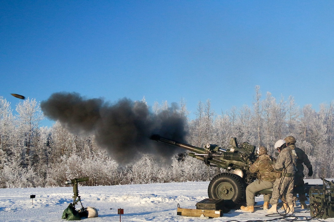 Paratroopers fire a howitzer in the snow.