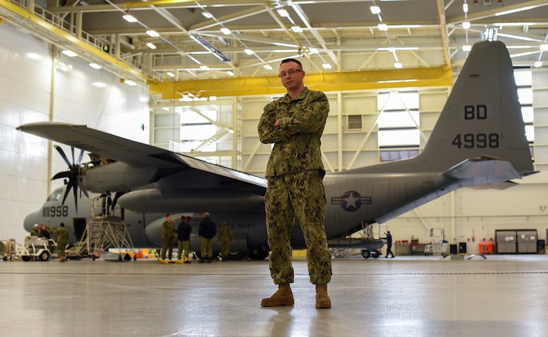 Petty Officer 1st Class William Martin, Fleet Logistics Support Squadron 64 (VR-64) aviation structural mechanic, poses in front of a C-130 Hercules in a hangar on Joint Base McGuire-Dix-Lakehurst, New Jersey, Dec. 12, 2018. Martin has been assigned to VR-64 for less than a year and has received every rank he has made on the first try. (U.S. Air Force photo by Airman 1st Class Ariel Owings)