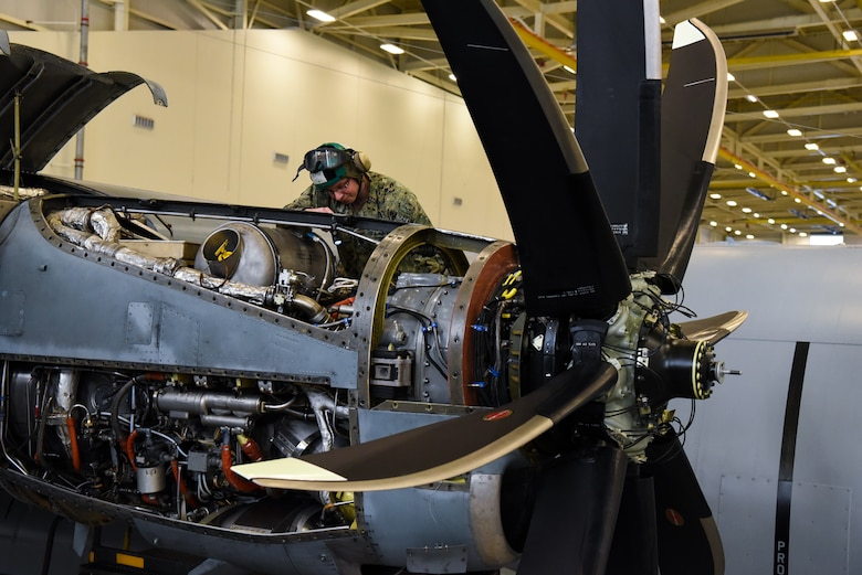 Petty Officer 1st Class William Martin, Fleet Logistics Support Squadron 64 (VR-64) aviation structural mechanic, works on an engine of a C-130 Hercules in a hangar on Joint Base McGuire-Dix-Lakehurst, New Jersey, Dec. 12, 2018. Since Martin started working in VR-64, the morale and work-ethic of the unit has increased, according to his peers, leaders and subordinates. (U.S. Air Force photo by Airman 1st Class Ariel Owings)
