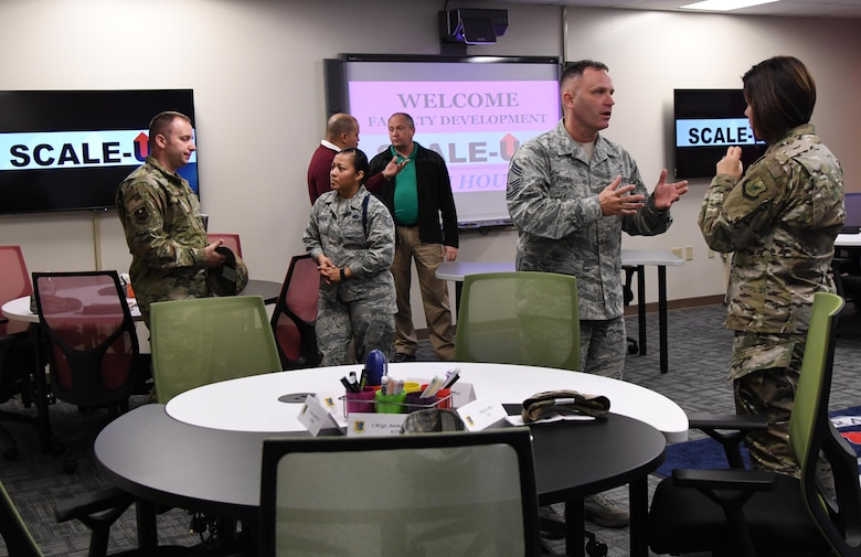 Keesler leadership and base personnel tour a classroom during the Student-Centered Active Learning Environment with Upside-down Pedagogies ribbon cutting ceremony inside Allee Hall at Keesler Air Force Base, Mississippi, Jan. 10, 2019. The SCALE-UP program was introduced by the 81st Training Support Squadron as a way to bring new technology and teaching techniques into Keesler classrooms to put more focus on students and their success in Air Force education. The new program has also brought a new way to teach basic skills like time management and critical thinking to the students while learning their career field. (U.S. Air Force photo by Kemberly Groue)