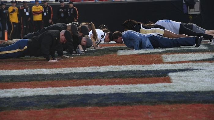 U.S. Army Soldiers perform push-ups after the Army scores, Dec. 22, 2018, at Fort Worth, Texas. The Army team scored 70 points during the Armed Forces Bowl.