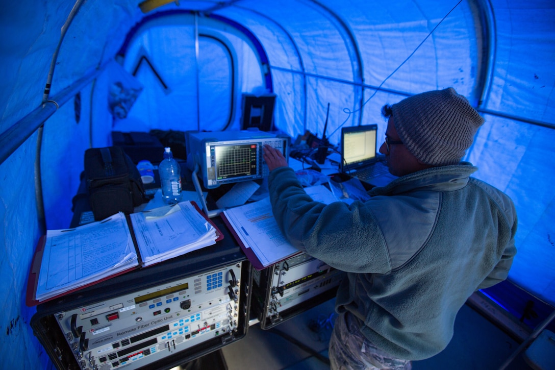 U.S. Air Force Staff Sgt. Titus Poulose of the 263rd Combat Communications Squadron with the North Carolina Air National Guard, operates communications equipment inside of a special cold-weather tent while deployed in support of Operation Deep Freeze (ODF), at McMurdo Station, Antarctica, Dec. 1, 2018. ODF is a military mission in support of the National Science Foundation throughout the continent of Antarctica, to provide air, land, and sea support to McMurdo Station. (Courtesy photo submitted by Civ. Johnny Chiang)