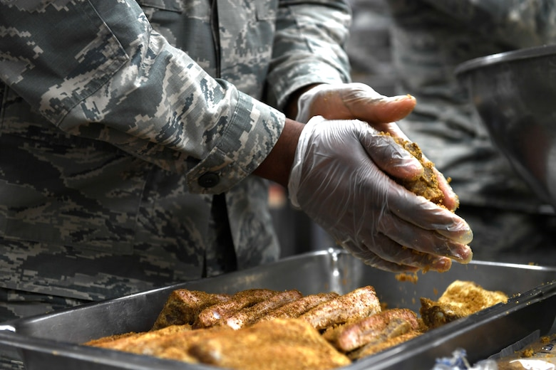 A member from the 145th Force Support Squadron rubs spices on ribs in preparation for lunch at the North Carolina Air National Guard Base, Charlotte Douglas International Airport, Jan. 12, 2019. Food services Airmen from the North Carolina Air National Guard train members from theNiagara Falls Air Reserve Station, New York, on full-service kitchen operations in preparation for the upcoming Air Force active duty and reserve Hennessy Award competition.