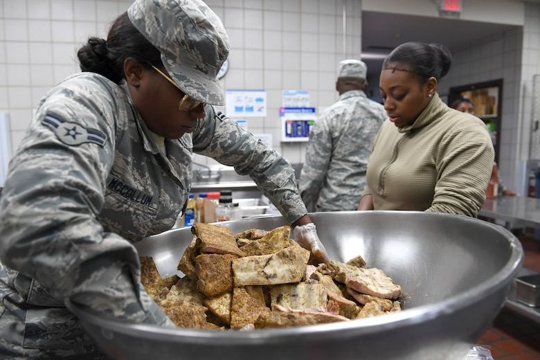 U.S. Air Force Airman 1st Class Pachea McCollum (left), 914th Air Refueling Wing, prepares lunch in the dining facility during drill weekend at the North Carolina Air National Guard Base, Charlotte Douglas International Airport, Jan. 12, 2019. Food services Airmen from the North Carolina Air National Guard train members from theNiagara Falls Air Reserve Station, New York, on full-service kitchen operations in preparation for the upcoming Air Force active duty and reserve Hennessy Award competition.