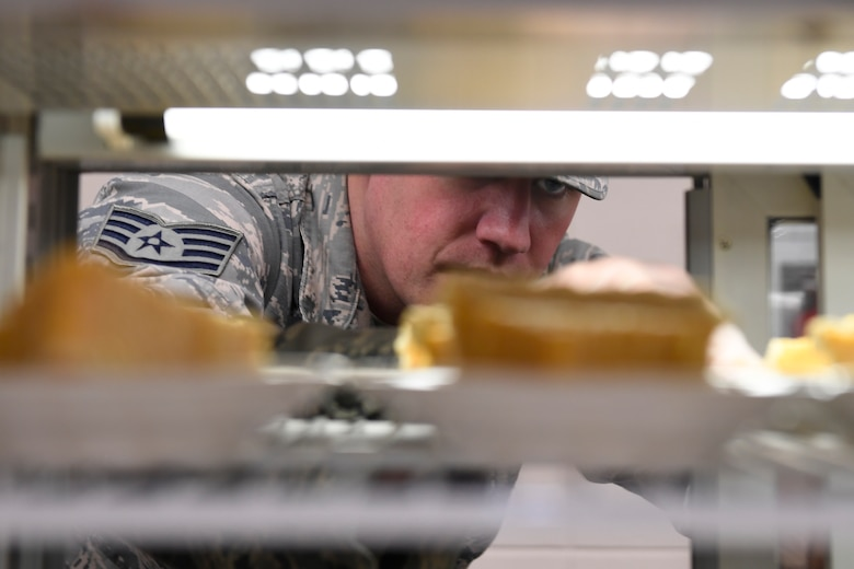 U.S. Air Force Staff Sgt. Jackson Hunt, 145th Force Support Squadron, places pumpkin pies in the display case for lunch in the dining facility during drill weekend at the North Carolina Air National Guard Base, Charlotte Douglas International Airport, Jan. 12, 2019. Food services Airmen from the North Carolina Air National Guard train members from theNiagara Falls Air Reserve Station, New York, on full-service kitchen operations in preparation for the upcoming Air Force active duty and reserve Hennessy Award competition.