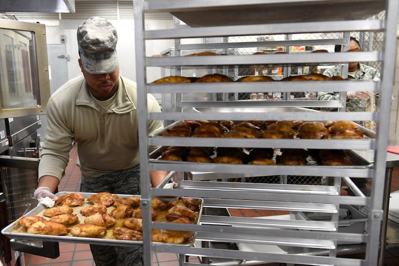 U.S. Air Force Senior Airman Deontre Barrett, 145th Force Support Squadron, places a pan of cooked chicken on a rack for lunch in the dining facility during drill weekend at the North Carolina Air National Guard Base, Charlotte Douglas International Airport, Jan. 12, 2019. Food services Airmen from the North Carolina Air National Guard train members from theNiagara Falls Air Reserve Station, New York, on full-service kitchen operations in preparation for the upcoming Air Force active duty and reserve Hennessy Award competition.