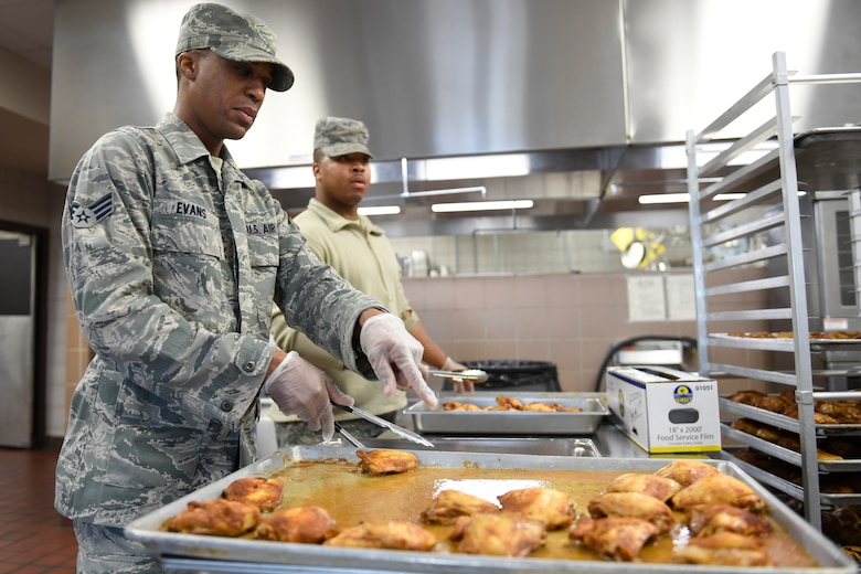 U.S. Air Force Senior Airman Derek Evans (left) Senior Airman Deontre Barrett (right), 145th Force Support Squadron, prepare cooked chicken to be served for lunch in the dining facility during drill weekend at the North Carolina Air National Guard Base, Charlotte Douglas International Airport, Jan. 12, 2019. Food services Airmen from the North Carolina Air National Guard train members from theNiagara Falls Air Reserve Station, New York, on full-service kitchen operations in preparation for the upcoming Air Force active duty and reserve Hennessy Award competition.