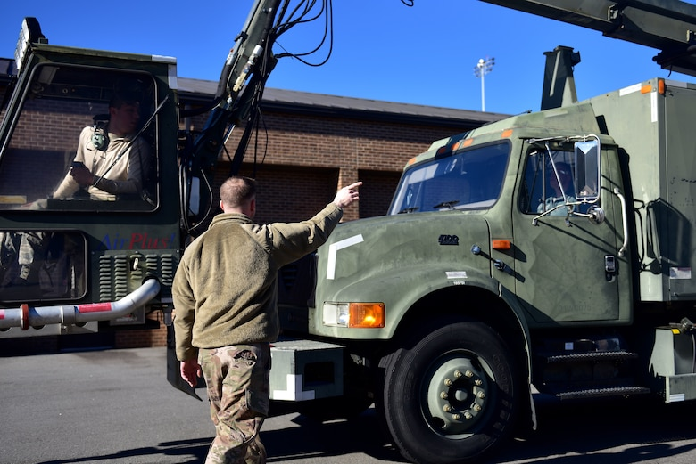 A man points at Airmen in a de-icing truck.