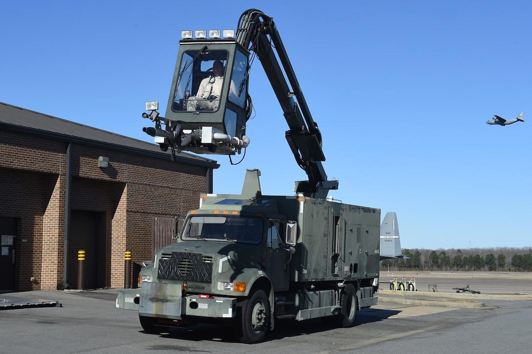 An Airmen is in a de-icing truck.