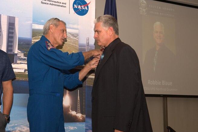 A man pins an award on another man