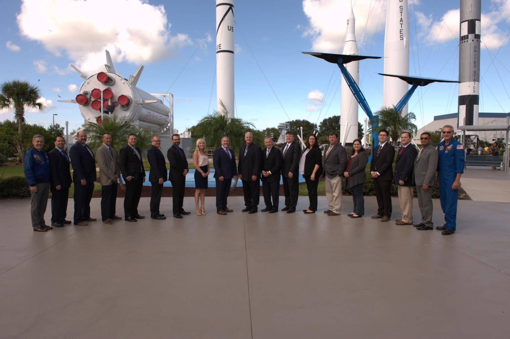 A group of people stand in front of an outdoor display of rockets
