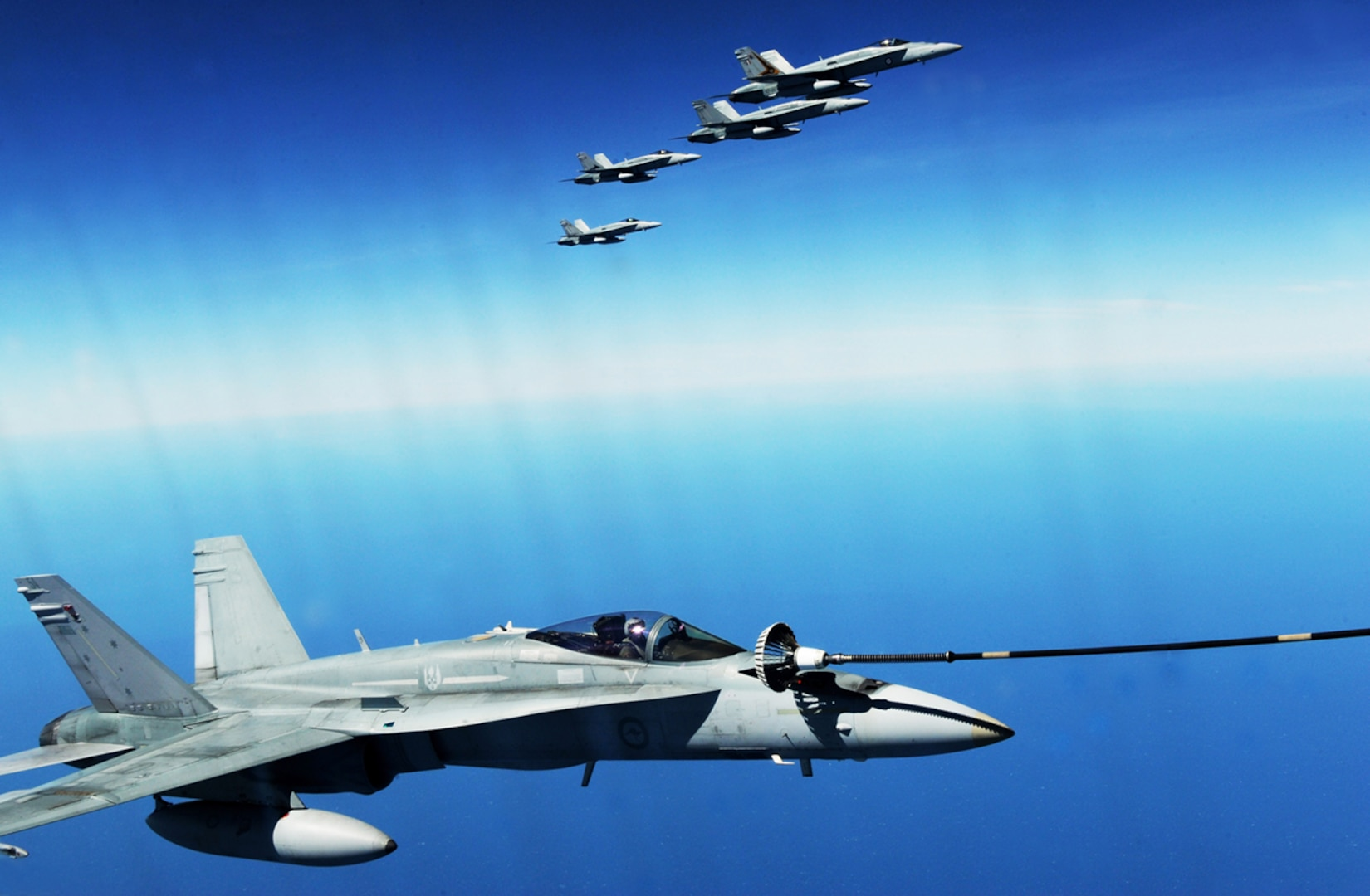 A Royal Australian air force F/A-18 Hornet refuels during a training exercise near Darwin, Australia. U.S. and Australian forces conduct air refueling missions throughout the exercise to improve interoperability and familiarization with each other's procedures.