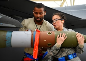 Staff Sgt. Albert Banks and Senior Airman Nadiya Frick, 309th Aircraft Maintenance Unit load crew team members, load an inert bomb onto an F-16 Fighting Falcon at Luke Air Force Base, Ariz., Jan. 10, 2019.