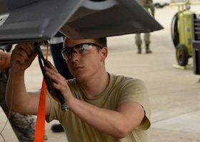 Airman 1st Class Joshua Elias, 309th Aircraft Maintenance Unit load crew team member, prepares to affix an inert bomb to an F-16 Fighting Falcon during the 56th Fighter Wing Quarterly Load Crew Competition at Luke Air Force Base, Ariz., Jan. 10, 2019.