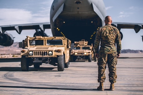 A Marine with 2nd Battalion, 7th Marine Regiment, 1st Marine Division watches as Airman with the 729th Airlift Squadron, Air Force Reserve Command, guide Humvees onto a C-17 Globemaster III at the Air Combat Element landing strip as a part of a rapid deployment ready exercise at the Marine Corps Air Ground Combat Center, Twentynine Palms, Calif., Nov. 28, 2018. The purpose of this exercise was to display 2nd Battalion, 7th Marine Regiment, 1st Marine Division capabilities to deploy its command assets anywhere around the world in 96 hours within a 24 hour notice. (U.S. Marine Corps photo by Lance Cpl. William Chockey)
