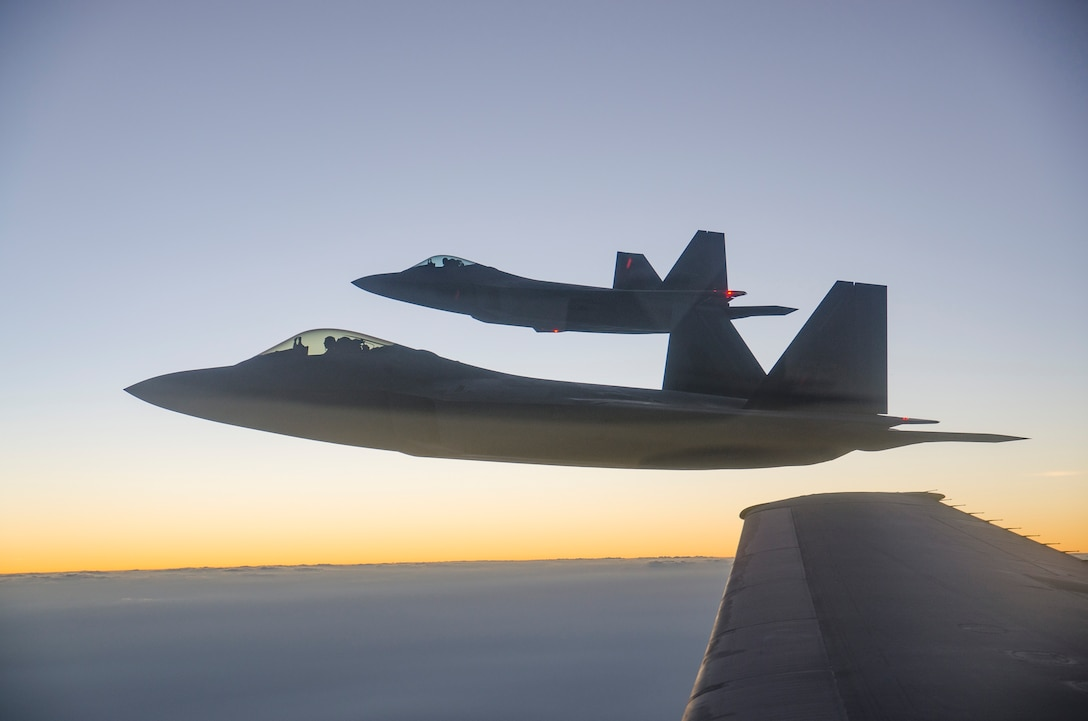 Two F-22 Raptors from the 94th Expeditionary Fighter Squadron, Al Dhafra Air Base, United Arab Emirates, fly in formation after refueling from a 908th Expeditionary Air Refueling Squadron KC-10 Extender over Southwest Asia, Sept. 12, 2018.