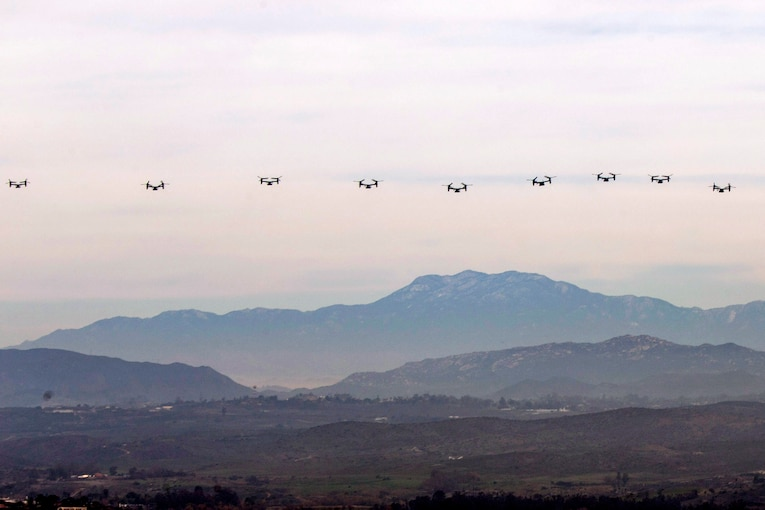 Nine tiltrotor aircraft fly in a horizontal row over a mountain range.