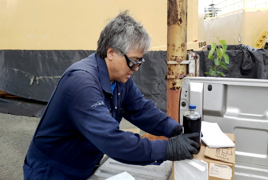 Defense Logistics Agency Energy Hawaii Quality Assurance Representative Daniel Muranaka handles a sample from one of Naval Facilities Engineering Command Hawaii fuel oil reclaimed tanks. The samples were delivered to Island Energy Services to conduct testing.