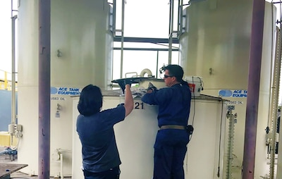 Naval Facilities Engineering Command Hawaii employees conduct sampling of fuel oil reclaimed.