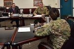 Three individuals hold meeting at a table, two military and one civilian