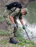 Seaman Ryan Shorter, who was training to become a medical corpsman at the Medical Education and Training Campus at Joint Base San Antonio-Fort Sam Houston, reaches for a piece of trash along Salado Creek during the annual Basura Bash Feb. 17, 2018.