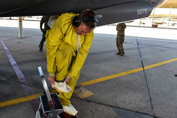 Tech. Sgt. Lance Dooley, a crew chief in the 466th Aircraft Maintenance Unit, prepares to crawl inside the intake of an F-35 Lightning II to perform a post-flight inspection
