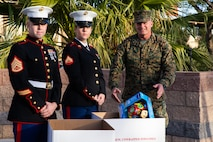 U.S. Marine Corps Brig. Gen. Roger B. Turner, Jr. (Right), commanding general, Marine Corps Air Ground Combat Center (MCAGCC), donates a gift to the Toys for Tots foundation, during the annual Marine Corps Communication and Electronics School (MCCES) Toys for Tots run, at MCAGCC, Twentynine Palms, Calif., Dec. 18, 2018. More than 2,000 participants purchased and ran with toys to donate to the U.S. Marine Corps Toys for Tots program. (U.S. Marine Corps Photo by Pfc. Aaron Harshaw).