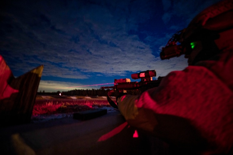 A soldier, illuminated in pinkish light, fires a weapon into a vivid blue night sky.