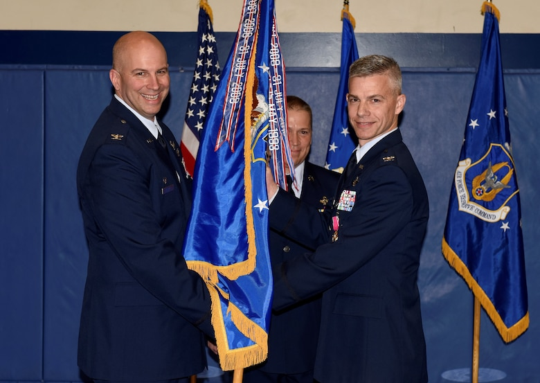 Col. Dean Sniegowski, 310th Space Wing commander, receives the 310th Operations Group guidon from Col. Stephen Slade, outgoing 310th OG commander, during a change of command ceremony Saturday, Jan. 5th, 2019.
