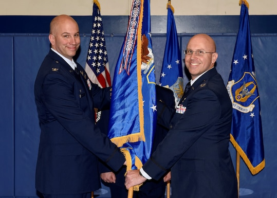 Col. Dean Sniegowski, 310th Space Wing commander, passes the 310th Operations Group guidon to Col. Leland Leonard, incoming 310th OG commander, during a change of command ceremony Saturday, Jan. 5th, 2019.