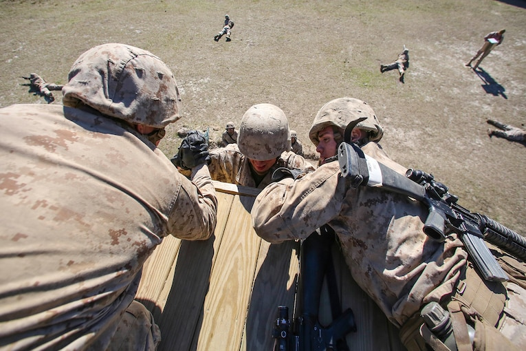 Marine Corps recruits help a fellow recruit over an obstacle.