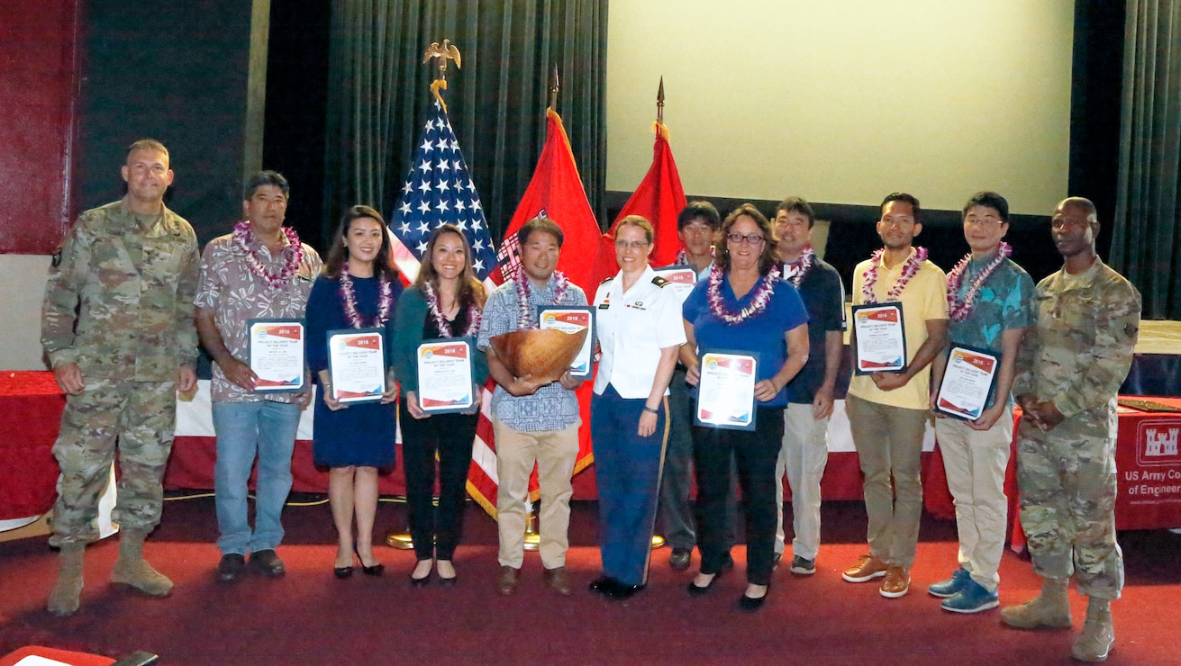 Project Manager Lance Sewake (center) and the FY16 PTA Repair Cespool Project Delivery Team accept the 2018 PDT of the Year Koa Bowl Award from Honolulu District Commander Lt. Col. Kathyrn Sanborn (center right)and Pacific Ocean Division Commander. Brig. Gen. Thomas Tickner (left) during the District's Annual Awards Townhall held Jan. 9, 2019.
