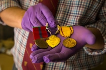 Owen Conner, uniforms and heraldry curator with the National Museum of the Marine Corps, inspects medal collection belonging to U.S. Marine Corps Sgt. Russell Rose at warehouse 2288, Marine Corps Base Camp Pendleton, California, Jan. 10, 2019. Several Marine Corps artifacts were collected from the MCB Camp Pendleton History Museum Branch for transport to the National Museum of the Marine Corps in Triangle, Virginia.