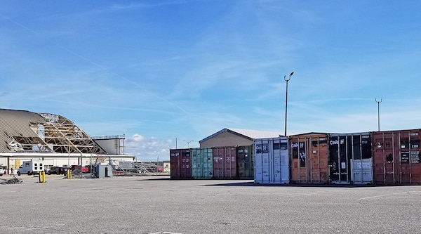 Excess shipping containers supplied from DLA Disposition Services line the parking lot of a damaged hangar facility at Tyndall AFB.