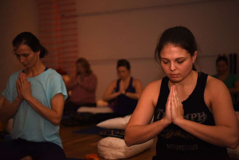 Team Mildenhall spouses practice Yin during a yoga session at a local yoga studio in Newmarket, England, Jan. 10, 2019. The yoga session was part of a Resiliency and Mindfulness Event hosted by Jack Sweet, RAF Mildenhall Community Support Coordinator, and RAFM Key Spouses organization. (U.S. Air Force photo by Airman 1st Class Brandon Esau)
