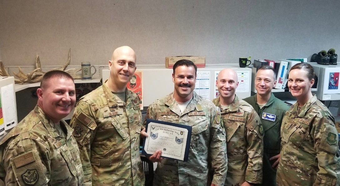 Staff Sgt. Raymond CaballeroPerez, 22nd Operations Support Squadron Survival, Evasion, Recovery and Escape operations and training NCO in charge, poses for a photo with wing leadership Dec. 19, 2018, at McConnell Air Force Base, Kansas. Perez was selected as an Air Mobility Command Stripes to Exceptional Performers promotee for his work as a SERE specialist. (Courtesy photo)