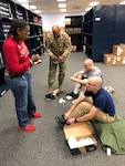 Air Force clothing initial issue section chief Vernalynne Carter and 502nd Logistics Readiness Squadron Commander Air Force Lt. Col Ernest Cage issue new American-made athletic footwear to Air Force recruits Daniel Sterling, right, and Ryan Padro, second right, at Joint Base San Antonio-Lackland, Texas, Jan. 3, 2019. Nearly 900 Air Force recruits were the first to receive the new item procured by Defense Logistics Agency as a result of the 2017 National Defense Authorization Act, which mandated the Department of Defense to provide American-made athletic footwear to enlistees upon their initial entry into the armed forces.
