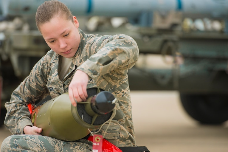 A woman sitting down holds a bomb.