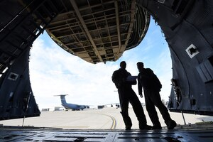 Tech. Sgt. Richard Bline, 312th Airlift Squadron loadmaster, left, and Staff Sgt. Phillip McHenry, 22nd Airlift Squadron loadmaster, right, discuss loading four U.S. Army UH-60 Black Hawks onto the C-5M Super Galaxy they're inside of January 13 at Travis Air Force Base, Calif. Bline and McHenry were afforded the rare opportunity to train on loading the aircraft as part of training focusing on full-spectrum readiness. (U.S. Air Force photo by Airman 1st Class Christian Conrad)