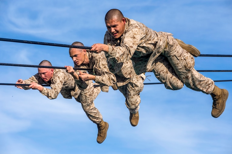 Three Marines slide across ropes as part of an obstacle.