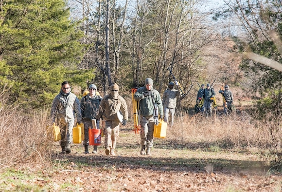 436th Civil Engineer Squadron engineering assistants carry necessary equipment to a debris field during an aircraft mishap survey exercise Dec. 18, 2018, near Killens Pond State Park, Kent County, Del. Survey team members located miscellaneous aircraft and aircrew items of a simulated T-38 Talon aircraft mishap and practiced plotting and documenting each of the items using GPS equipment and a digital camera. (U.S. Air Force photo by Roland Balik)