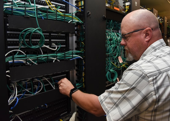 Gilbert Wheeler, 47th Medical Support Squadron information systems flight chief, arranges wires in the communications closet at the Laughlin Air Force Base, Texas medical clinic, Jan. 14, 2019. Wheeler stays busy at the 47th Medical Group, ensuring hundreds of thousands of dollars' worth of equipment remains up-to-date and available to help Laughlin medics care for patients. (U.S. Air Force photo by Airman 1st Class Anne McCready)