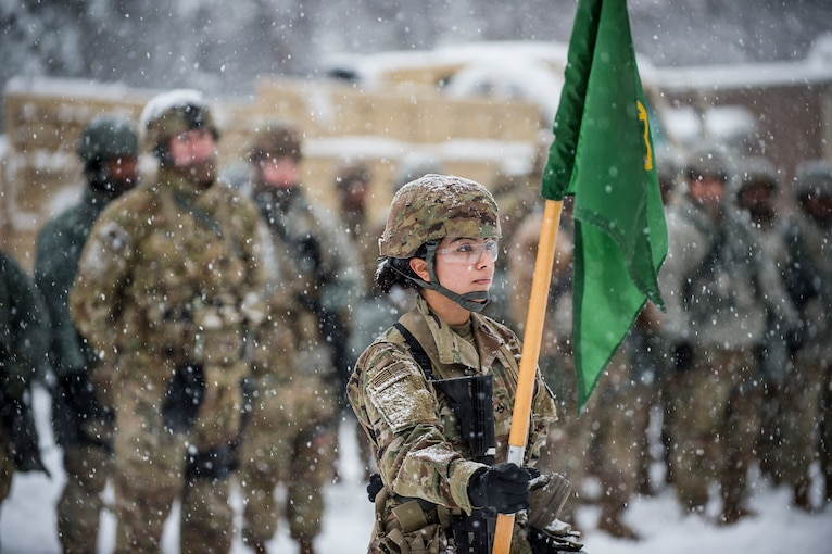 A soldier stands in the snow holding a flag with a group of soldiers behind her.