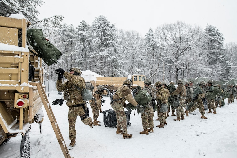 A group of soldiers stand in a line loading a truck in the snow.