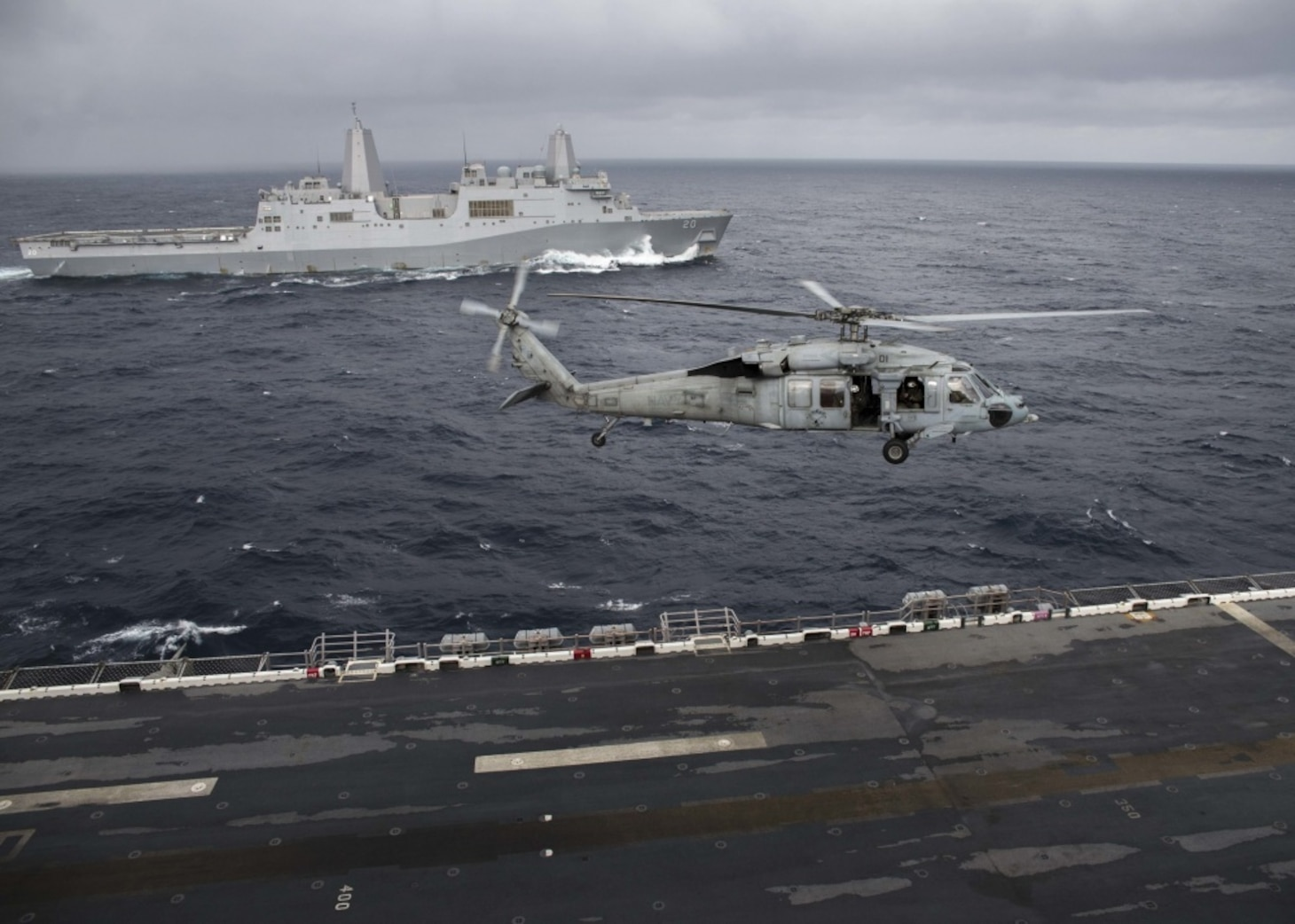 """EAST CHINA SEA (Jan. 12, 2019) - A MH-60S Sea Hawk helicopter, assigned to the """"Island Knights"""" of Helicopter Sea Combat Squadron (HSC) 25, passes in front of the amphibious transport dock ship USS Green Bay (LPD 20) as it prepares to land on the flight deck of the amphibious assault ship USS Wasp (LHD 1). Wasp, flagship of Wasp Amphibious Ready Group, is operating in the Indo-Pacific region to enhance interoperability with partners and serve as a ready-response force for any type of contingency."""